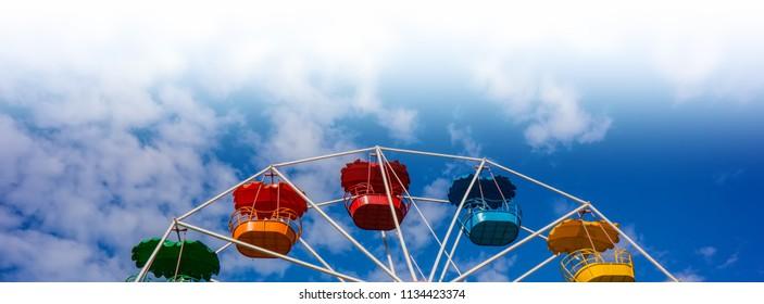 Ferris wheel against the blue sky. Horizontal banner.