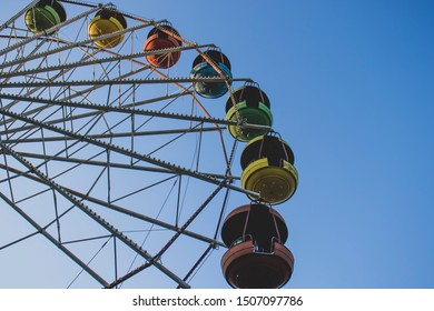 Ferris wheel against the blue sky. Fairytale background and wallpaper.