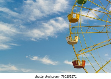 Ferris wheel - amusement device in the form of a large, vertical-mounted wheel, the rim of which is attached cabins for passengers. Blue clear sky, altocumulus clouds (lat. Altocumulus)