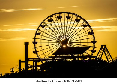 A ferris wheel at an amusement park stands out against a beautiful sunset and golden sky