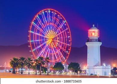 Ferris wheel at amusement theme park in the evening time. Batumi Boulevard. Photo is taken with a long exposure and has motion blur.