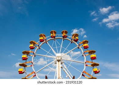Ferris wheel with bright colored cabins in amusement park against blue sky and white clouds.