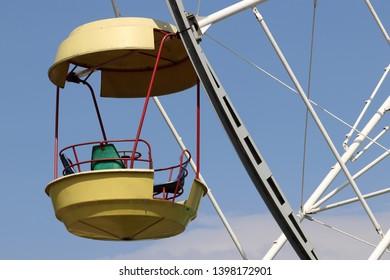 Ferris wheel cabin on blue sky background. Damn wheel in amusement park