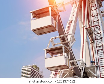 Ferris wheel cabins view. Blue sky and sun light background