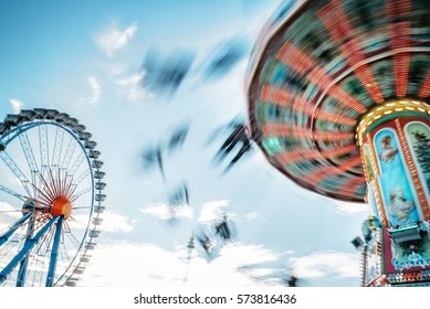ferris wheel and carousel in motion blur at Oktoberfest in Munich