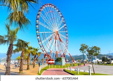 Ferris wheel, city landscape, palm trees and mountain peaks of Batumi, Georgia summer Black sea resort