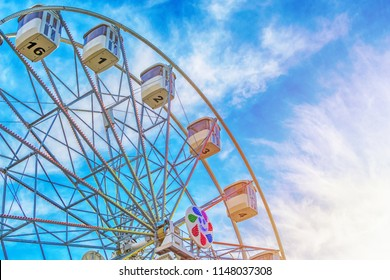 Ferris wheel close up on cloudy blue sky with sunlight