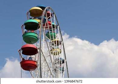 Ferris wheel with colourful cabins against blue sky and white clouds. People ride the damn wheel in amusement park