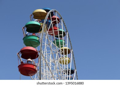 Ferris wheel with colourful cabins isolated on clear blue sky background. People ride the damn wheel in amusement park