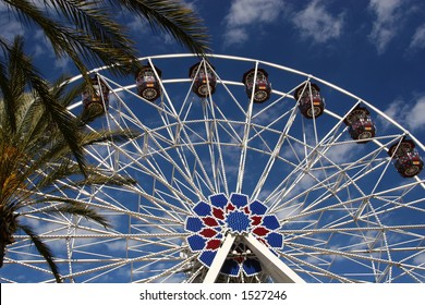 A ferris wheel framed by palm trees at an outdoor shopping center in Irvine, California.