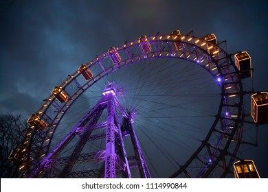 Ferris wheel with light between clouds. London eye. Winter. Night sky and clouds. England. Great Britain