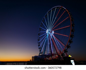 ferris wheel lit up red, white and blue at sunset