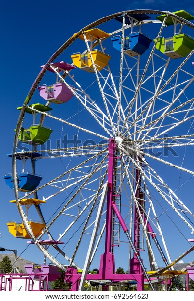 Ferris wheel at local summer carnival with brightly colored seats