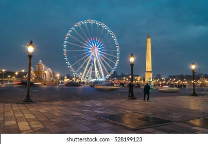 Ferris wheel and the Luxor Obelisk on the Concorde square (Place Concorde) in the Christmas time at night. The Luxor Obelisk is originally located at the entrance to Luxor Temple, in Egypt.