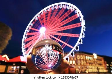 Ferris wheel on the Duesseldorfer Burgplatz with a view through a glass ball