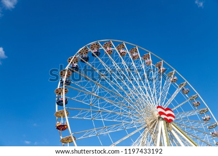 Ferris wheel on a fairground in front of a blue sky.