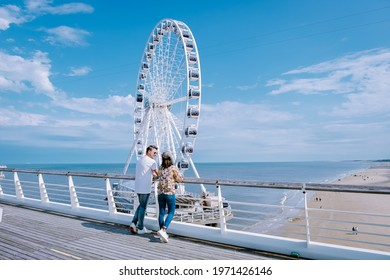 The Ferris Wheel The Pier at Scheveningen, The Hague, The Netherlands on a Spring day, couple man and woman mid age on the beach