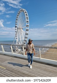 The Ferris Wheel The Pier at Scheveningen, The Hague, The Netherlands on a Spring day, young woman on the beach