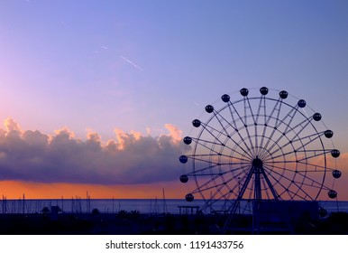 Ferris wheel silhouette, ocean with fishing boats in the background.