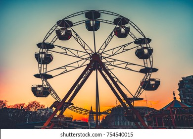 Ferris wheel Silhouette at sunset against the colorful evening skyline at dusk - popular children attraction in park. Vintage retro toning filter