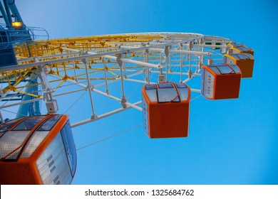 Ferris wheel in Tbilisi bottom view and blue sky Park attraction with evening light