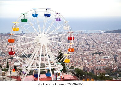 Ferris wheel in Tibidabo Amusement Park, in Barcelona, Spain. Aerial view of Barcelona city seen from the Sagrat Cor church on top of the hill.