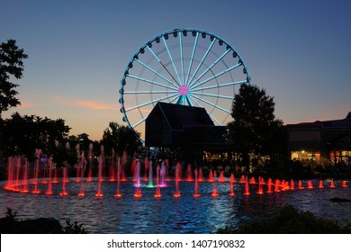 Ferris wheel and water fountain with colored lights at dusk
