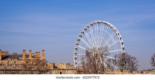 Ferris wheel, York city walls and 18 Century building.