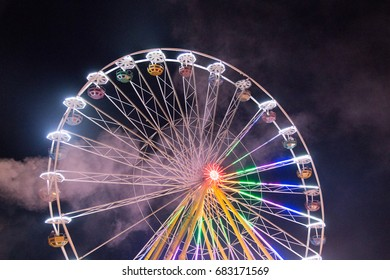 ferris wheels spinning with colorful lightpainting on a bavarian fair in germany at night, shot with long exposure and dust and smoke
