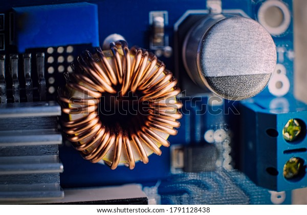 Ferrit inductance coil on electric board wrapped with copper wire along with other components, macro shot