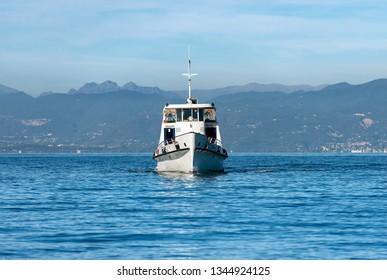 Ferry boat in the Lake Garda (Lago di Garda) in front of the port of Lazise, small town in Veneto, Italy, Europe