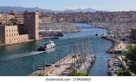 Ferry boat sails past historical fortifications into the old harbor of Marseille, France