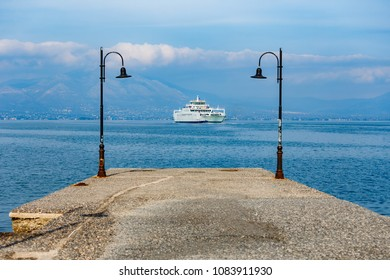 Ferry boat traveling across the sea with pier lamps framing the scene against a cloudy sky in Greece