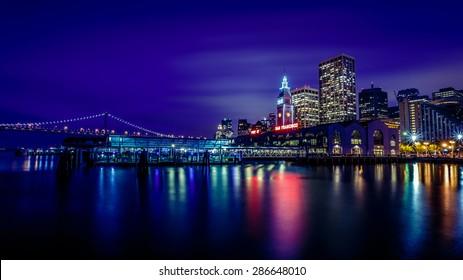 Ferry Building and Bay Bridge illuminated at night in San Francisco, California, USA
