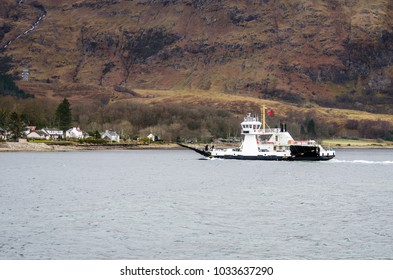 Ferry Crossing a Lake in Scotland on a Winter Day. A Towering Mountain is in Background
