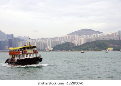 a ferry crossing the Victoria Harbour towards Sai Wan Ho in Hong Kong, with many buildings at background (Translation: Kwun Tong to Sai Wan Ho)