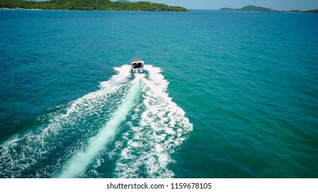 Ferry at the Gulf of Siam. Aerial view of floating ferry at sunset. Colorful landscape with boat, turquoise sea. Top view from drone of yacht. Seascape with motorboat