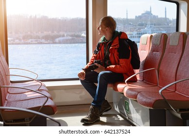 Ferry over Bosporus in Istanbul, Turkey. Interior of a ship with man passenger, red seats and sea view.