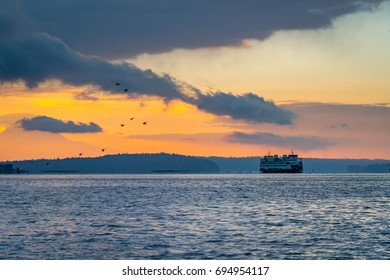 Ferry passing through Rich Passage on Puget Sound at sunrise while a flock of geese takes flight, Mount Rainier in the background