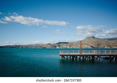 Ferry pier on the lake called Lago General Carrera in small town Puerto Ibanez in Chile. Chilean Patagonia view of glacial lake water against mountains and blue sky. Biggest lake in Chile.