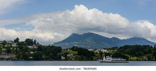 A ferry plying in Lake Luzern against a backdrop of cottages, lush green hills and a cloudy sky.