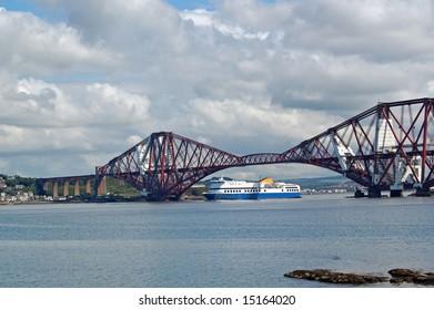 ferry sailing under the forth rail bridge in scotland