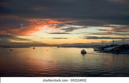 Ferry in the sunset, passing Tjuvholmen, Oslo.