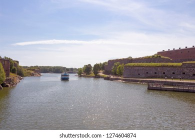 The ferry swims to the pier and the ancient fortifications in the historic island fortress Suomenlinna, Sveaborg in the Gulf of Finland in Finland on a summer day.