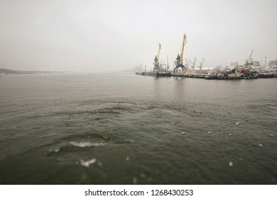 ferry trip in Lithuania to the city of Klaipeda in the winter season overlooking the bay with access to the Baltic Sea, and with cranes in the port