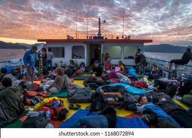 Ferry from Wakai to Gorontalo, Sulawesi, Indonesia - July 21 2015: Sunrise on deck with sleeping tourists on the ferry