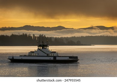 Ferryboat and the Cascade Mountains. A ferryboat makes the crossing to its island destination in the Puget Sound area of western Washington state. The Cascades mountains are seen in the background.