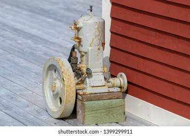 Ferryland, Newfoundland/Canada - May 2019: An antique Acadia Make n Break inboard engine known as a putt-putt motor sits on a wooden deck  near a red fishing stage.