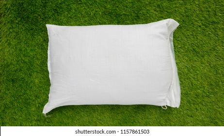 Fertilizer and soil white bag on green grass background