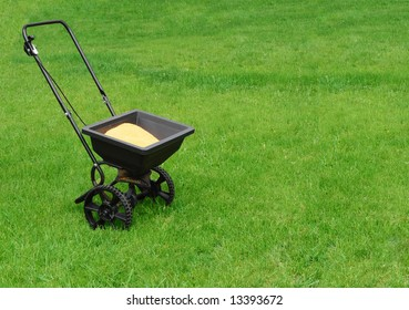 Fertilizer spreader on green grass background